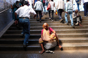 The woman sat on the steps and the commuters parted around her like river water around a stone.